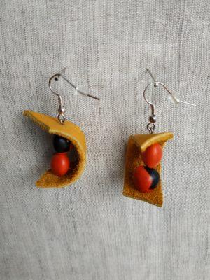 Boucles d'oreilles en gros plan sur fond gris.2 graines de caconnier et lamelle de cuir jaune par boucle d'oreille