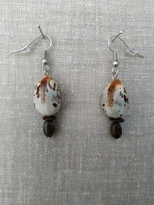 Boucles d'oreilles en acier rhodié. Graines de ricin une grande et une petite et monval. Le bijou est présenté sur fond gris