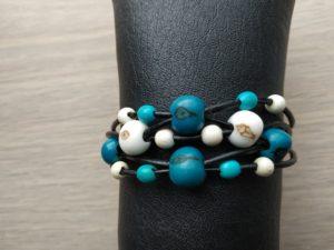 Bracelet en cuir noir, 5 brins. 4 graines d'acaï bleues, 2 graines d'acaï blanches. 6 graines de toloman blanches et 4 graines de toloman bleues. Fermoir mousqueton en métal rhodié. Bracelet ajustable grâce à sa chaînette d'extension. Bracelet présenté sur un boudin simili cuir noir moussé