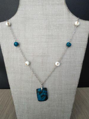 collier en acier rhodié. 4 graines d'açaï rondes blanches et 2 bleues. Une plaque marbrée de tagua tintée en bleue. Image vue de loin. Bijou présenté sur présentoir gris