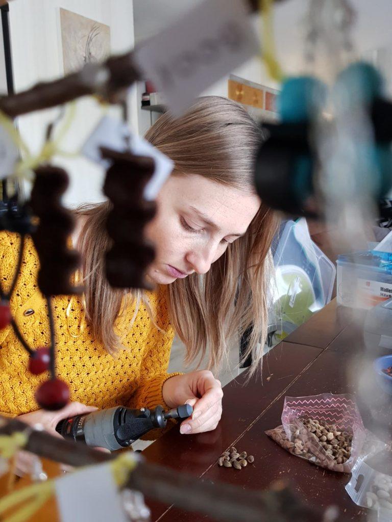 Ici la créatrice d'Au gré de mes envies en train de poncer des graines de catalpa afin de pouvoir les utiliser dans la création de ses bijoux.