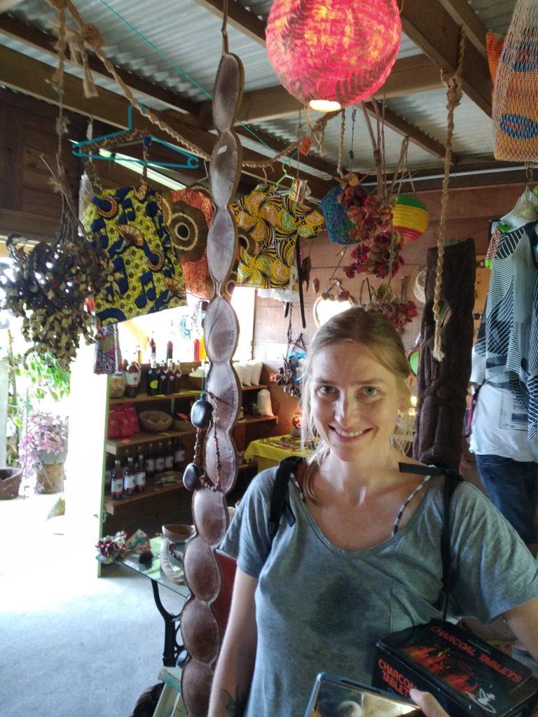 photo de la créatrice Stéphanie en Martinique avec dans le fond des gousses et graines des Antilles